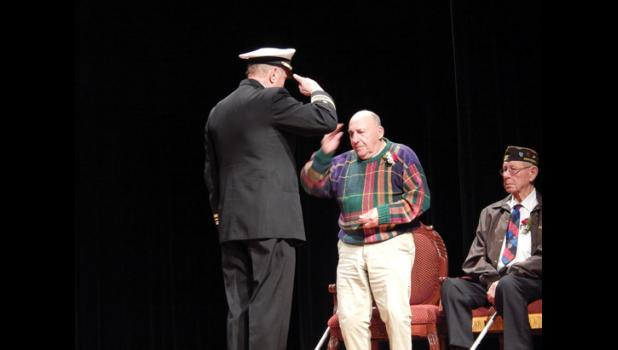 """Navy Lieutenant Commander Graham Clark, who was on Yankee Station aboard the USS Oriskany in the Tonkin Gulf during the Vietnam War, salutes WWII veteran and former Navy Ship's Cook Second Class Troy Scatterella (left) after presenting him with a World War II Victory Coin along with a commemorative coin from the San Diego Naval Base. Former Army PFC Harold """"Bud"""" Biskey (right) also received a World War II Victory Coin along with coins commemorating his Bronze Star and Purple Heart from USAF Captain Tony Fo"""